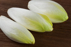 Chicoree. Green chicory washed on a wooden board Stock Photos