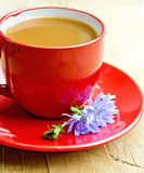 Chicory drink in red cup with flower on saucer Stock Photo