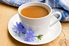 Chicory drink in white cup with flower on board Royalty Free Stock Photo