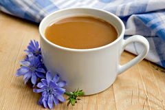 Chicory drink in white cup with flower on board Stock Photos