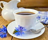 Chicory drink in white cup with milkman on board Royalty Free Stock Image