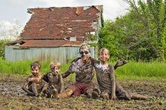 Chicos del campo que juegan en fango Imágenes de archivo libres de regalías