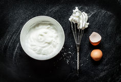 Chicoteamento claras de ovos em uma receita da espuma no preto Foto de Stock Royalty Free