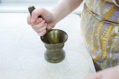 Chicoteando cravos-da-índia em um almofariz. Imagens de Stock Royalty Free