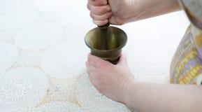 Chicoteando cravos-da-índia em um almofariz. Imagens de Stock