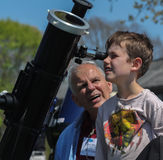 Boy looking through telescope with senior man Stock Image