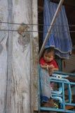Chid som ser ut ur koja i byn Tan Chau Royaltyfri Foto