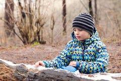 Chidl palying z roztapiającym śniegiem w lesie Fotografia Royalty Free