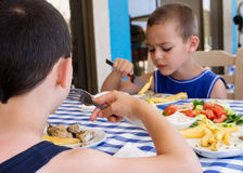 Chidlren eating lunch at table Royalty Free Stock Photography