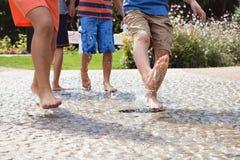 Chidlren nu-pieds jouer à la fontaine d'eau Images stock