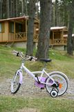 Chidren pink bicycle in wooden cabin mountain. Pine camping Pyrenees Royalty Free Stock Photos
