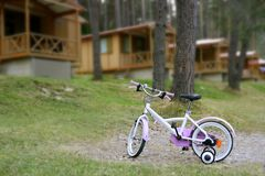 Chidren pink bicycle in wooden cabin mountain. Pine camping Pyrenees Stock Images