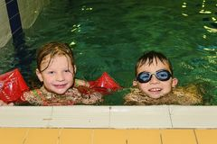 Chidren in public pool. Girl wears armband floats and boy with swimming goggles. stock image