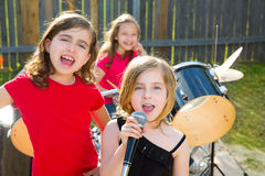 Chidren singer girl singing playing live band in backyard. Blond kid singer girl singing playing live band in backyard concert with friends Stock Image