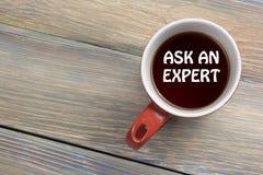 Chieda ad un esperto Tazza di caffè con il messaggio Vista del piano d'appoggio della scrivania fotografia stock libera da diritti
