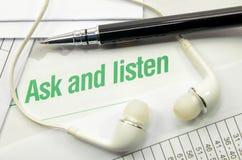Chieda ed ascolti stampato su un libro fotografia stock