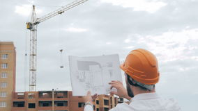 Chief architect at construction site. Chief architect in a hard hat at construction site looking at the plan, blueprint. stock video