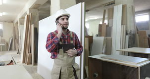 The chief carpenter in the joinery uniform and a white helmet answers the phone call. stock footage