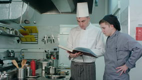 Chief chef holding recipe book and explaining something to his young trainee stock footage