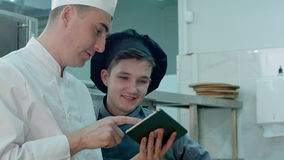 Chief chef showing cook trainee in hat something funny on digital tablet stock video