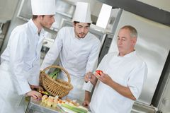 Chief chef watching assistants garnishing dish. Chief chef watching his assistants garnishing a dish royalty free stock image
