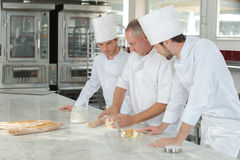 Chief chef watching assistants garnishing dish. Chief chef watching his assistants garnishing a dish stock images