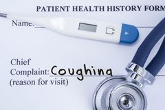 Chief complaint coughing. Paper patient health history form, on which is written the complaint coughing as the main reason for vis royalty free stock photography