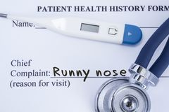 Chief complaint runny nose. Paper patient health history form, on which is written the complaint runny nose as the main reason for royalty free stock photos