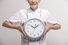 Chief cook. Close-up. Time to dinner. Senior male chief cook in uniform holding a clock on grey background Royalty Free Stock Photo