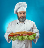 Chief cook holding big sandwich Stock Image