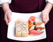 Chief cook holding plate with sushi Stock Images