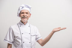 Chief cook. Senior male chief cook in uniform on grey background Royalty Free Stock Images