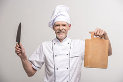 Chief cook. Senior male chief cook in uniform holding knife and  chopping board a  on grey background Stock Photos
