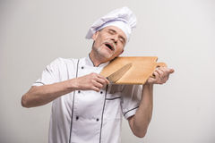 Chief cook. Senior male chief cook in uniform holding knife and  chopping board a  on grey background Stock Photography
