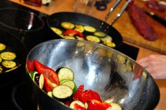 Chief cooks fried vegetables on pan Stock Images