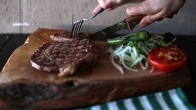 Chief cuts meat with knife. With wooden cutting board on table stock video footage