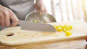 Chief cutting red bell peppers on a wooden board with a professional knife. Royalty Free Stock Photo