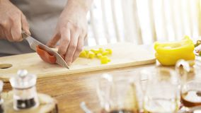 Chief cutting red bell peppers on a wooden board with a professional knife and a great skill. Stock Photos