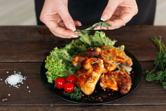 Chief decorated spicy chicken on wooden table Royalty Free Stock Photos