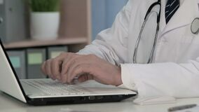 Chief doctor typing text on laptop keyboard, keeping electronic medical records. Stock footage stock video footage