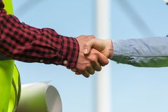 Concept of engineers and windmills. Chief executive of a women and a men engineer in green waistcoats are shaking hands against the backdrop of a windmill Stock Photo