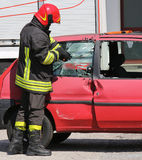 Chief fireman while breaking the glass of a car with a special e Stock Photo
