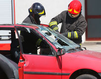 Chief fireman whit red helmet while breaking the windshield of a Royalty Free Stock Photo