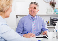 Chief gives task to assistant. Mature chief gives task to assistant at office at table royalty free stock images