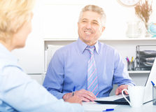 Chief gives task to assistant. Mature chief gives task to assistant at office at table royalty free stock image