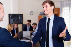 Chief greeting a employee and shaking hands. Chief greeting a new employee and shaking hands in office royalty free stock photos