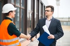 Chief handshaking with workers engineers and giving salary in an envelope. Good job. Business modern background. Boss or Chief handshaking with workers stock photography