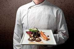 Chief holding tray with roasted salmon fillet Stock Images
