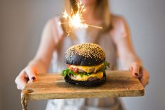 The chief is holding a wooden cutting Board with a black Burger. stock photography