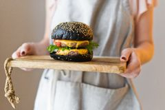 The chief is holding a wooden cutting Board with a black Burger. royalty free stock photo